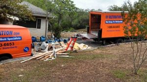 Water Damage Restoration Van And Truck With Debris Outside